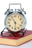 Book with alarm clock and eyeglasses Royalty Free Stock Image