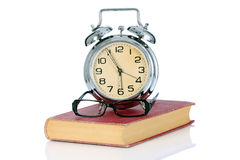 Book with alarm clock and eyeglasses Stock Photography