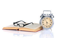 Book with alarm clock and eyeglasses Stock Image