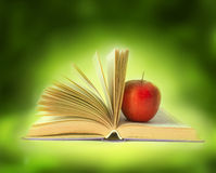 Book with apple in bright background Stock Photography