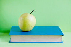 Book and apple on green background Royalty Free Stock Images