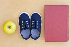 Book, apple, sneakers Royalty Free Stock Photo