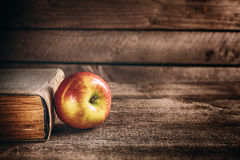 Book and apple on the wooden table Royalty Free Stock Image