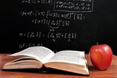 Book and Apple on wooden table in front of blackboard where is mathematical equation in the classroom. Red Apple and books on wooden table and school blackboard royalty free stock images