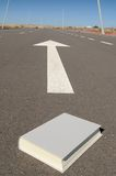 Book and arrow on a asphalt street to the future Stock Photography