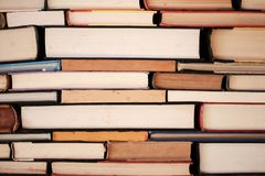 Book background - view of edge of old hardback books stacked almost like bricks - closeup.  royalty free stock images