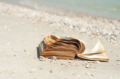 Book on the beach. Paper book lying on the sand on the beach near the sea on a sunny summer day surrounded by shelves Royalty Free Stock Images
