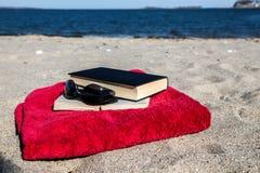 Book on beach with blue ocean Stock Photos
