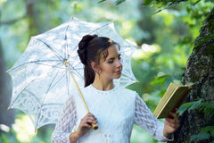 With a book Beautiful laughing bride with decorative umbrella Royalty Free Stock Photo