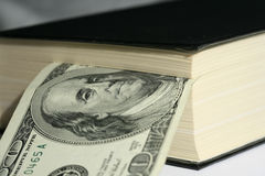 Book and bill. Close-up of one hundred dollars bill in the black book Royalty Free Stock Photo