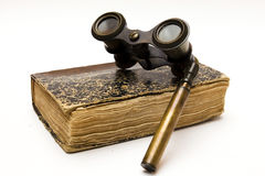 Book and binoculars. Book on binoculars old, wearing glasses upwards Royalty Free Stock Photography