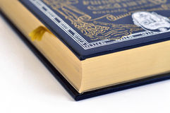 A book with a black cover and edge gilding. A gilt-edged book with a black patterned cover and a bookmark stock photography