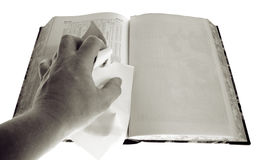 Book blank page censorship. Hand tears page out of book. To disagree with the text or censorship. Old book and hand isolated on white stock photography