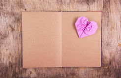A book with blank pages and an origami heart on a wooden background. Royalty Free Stock Images