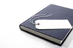 A book with a blank tag. A book laying down with a blank tag on top of it Stock Photos