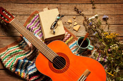 Book, blanket, coffee and classic guitar on wood. Late summer or autumn relaxation, rustic background on wood from above. Country lifestyle, rural vacation or Royalty Free Stock Photography
