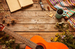 Book, blanket, coffee and classic guitar on wood. Late summer or autumn relaxation, rustic background on wood from above. Country lifestyle, rural vacation or Stock Photos