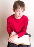 This book is so boring - Teen rolling his eyes Stock Photo