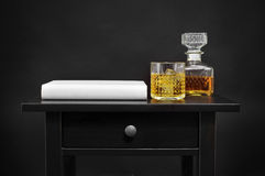 A book, a bottle and a glass with liquor on a table, over a blac. A book, and a bottle and a lowball glass with liquor on a black table, over a black background Royalty Free Stock Image