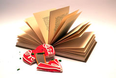 The book and the broken heart. Open book with broken l biscuit heart in front Royalty Free Stock Photo