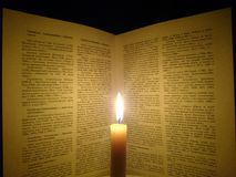 Book and a burning candle. Book of reference behind a burning candle Royalty Free Stock Photo