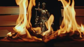 The concept of lawlessness, corruption, destruction. The book burns with a bright flame on the background of the statuette of the lady of justice and books. The stock footage