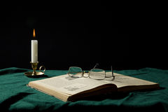 Book and candle. Old book, candle and eye-glasses Royalty Free Stock Photo