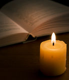 Book in candlelight. Open book and burning candle on dark Stock Photo