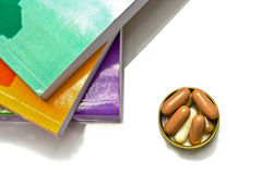 Book and  capsule pills Stock Photos