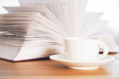Book and ceramic coffee cup. Open book and ceramic coffee cup on wooden table Stock Photos
