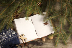 Book with Christmas decoration on the wooden rustic table. Open book with Christmas decoration on the wooden rustic table Royalty Free Stock Photos