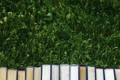Book closed books are on the green grass royalty free stock photography