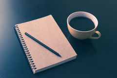 Book and coffee cup on black wooden table Stock Photos
