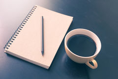 Book and coffee cup on black wooden table Royalty Free Stock Image