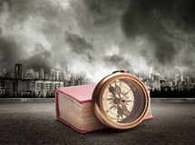 Book and compass on view of city in stormy sky Stock Images