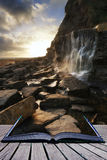 Book concept Beautiful landscape image waterfall flowing into rocks on beach at sunset stock photo