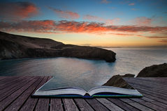 Book concept Beautiful vibrant sunrise over rocky coastline Royalty Free Stock Photos