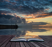 Book concept Beautiful vibrant sunrise sky over calm water ocean. Book concept Stunning sunrise over ocean with lighthouse and harbor wall Stock Images
