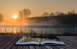Book concept Landscape of lake in mist with sun glow at sunrise Stock Images