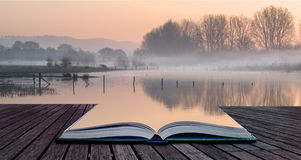 Book concept Landscape of lake in mist with sun glow at sunrise Stock Photos