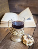 Book, cookies and tea in coaster on wooden background Stock Photos