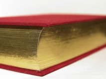 Book Corner. Closeup of the corner of a gold-gilded book with a red cover Royalty Free Stock Photos