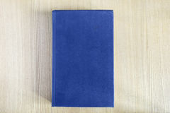Book cover. Book with blue blank cover on wooden table Royalty Free Stock Images