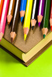 Book and crayons on green Stock Photos