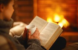 Book and cup of coffee in hands of girl on winter evening near. Book and cup of coffee in hands of girl on winter autumn evening near fireplace stock image