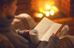 Book and cup of coffee in hands of girl on  winter evening near. Book and cup of coffee in hands of girl on winter autumn evening near fireplace Royalty Free Stock Image