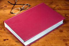 Book on Desk with Glasses. This is an image of a red book on a wooden desk with glasses stock photography
