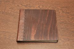 Book on a desk. Note book with hard wooden cover stock images