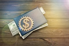 Book, dollar sign in a wooden gear on a wooden background. Business, finance. money deposits royalty free stock photos