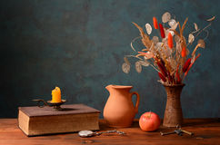 Book and dried flowers in a ceramic vase Stock Image